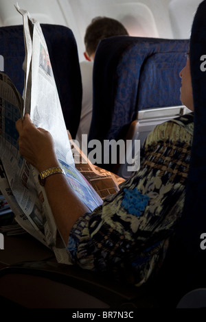 Airplane passenger reading newspaper in first class on flight - Stock Photo