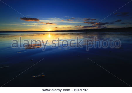 Sunset reflected in the wet sands left by the receding tide in Mount's Bay, Cornwall. - Stock Photo