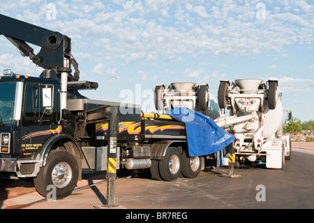Concrete trucks feed a boom truck used for pumping concrete for a new house under construction in Arizona. - Stock Photo