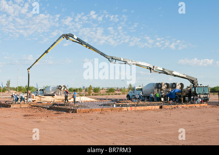 A crew of workers pour concrete from a boom truck for the floor of a new house in Arizona. - Stock Photo