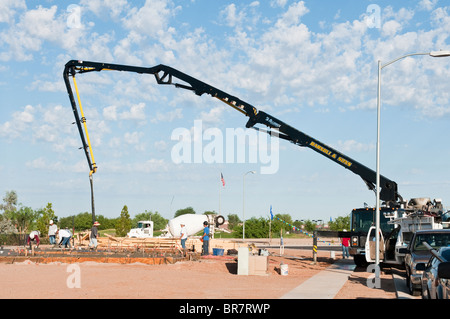 A crew of workers pour a concrete slab for a new house under construction in Arizona. - Stock Photo