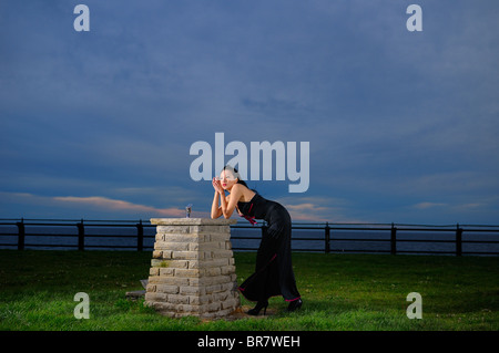 Woman in evening dress leaning on drinking fountain at RC Harris water treatment plant on Lake Ontario Toronto - Stock Photo
