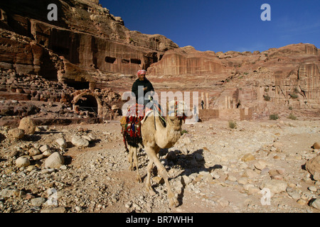 Man on camel in front of theater at Petra, Jordan - Stock Photo