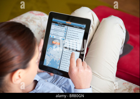 Woman using iPad tablet computer to book holiday using online Kayak travel application - Stock Photo