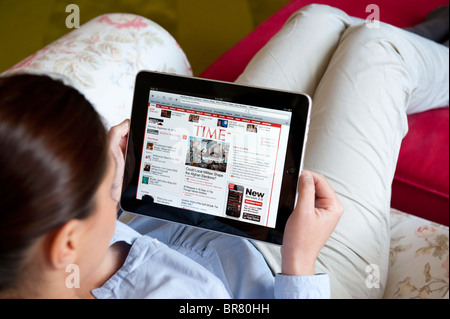 Woman using iPad tablet computer to read Time magazine online - Stock Photo