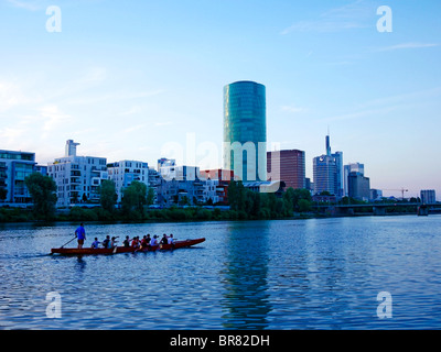 Rowing boat passing in front of Frankfurt Westhafen quarter at dusk - Stock Photo