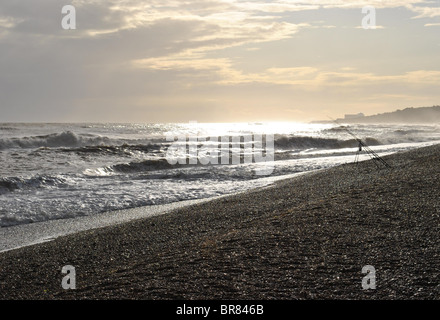 Dunwich beach at dusk with a lone fishing rod and the faint silhouette of Sizewell Nuclear power station in the - Stock Photo