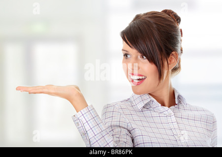 Young happy businesswoman presenting something on her hand - Stock Photo