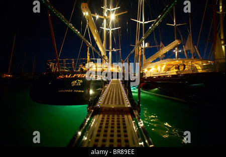 Superyachts lit up at night in Gustavia during the St Barts Bucket, Saint Barthelemy, Caribbean. - Stock Photo