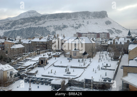 A wintry urban landscape, looking over the 17th century Canongate Kirk towards Salisbury Crags and Arthur's Seat - Stock Photo