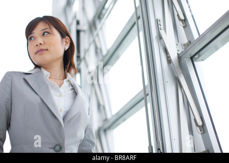 Young businesswoman standing by window, looking away - Stock Photo