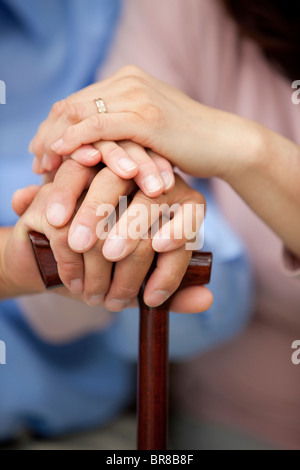 Mature couple stacking hands on top of each other, close up - Stock Photo