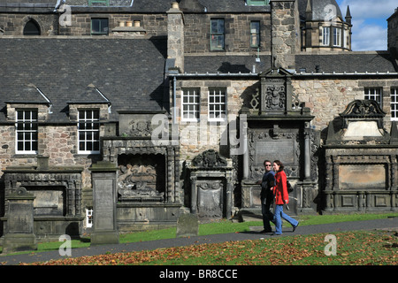 A couple walking by 17th century mural monuments in Greyfriars Kirkyard in Edinburgh, Scotland. - Stock Photo
