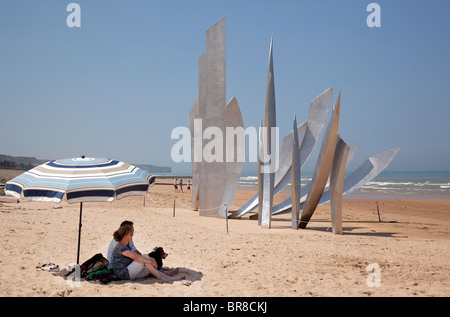 Visitors on the beach by the the monument to Allied troops at Omaha Beach Normandy France - Stock Photo
