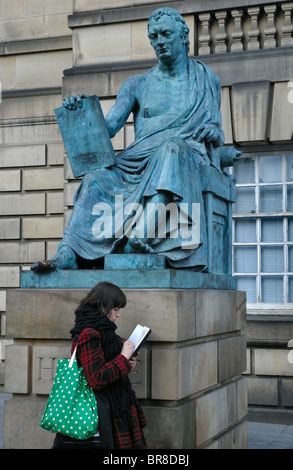 A girl sketches beside the statue of David Hume on the High Street in Edinburgh, Scotland. - Stock Photo
