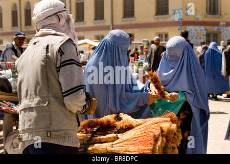 Two women in burqas shop for brooms near Mandawi Market in Kabul. - Stock Photo
