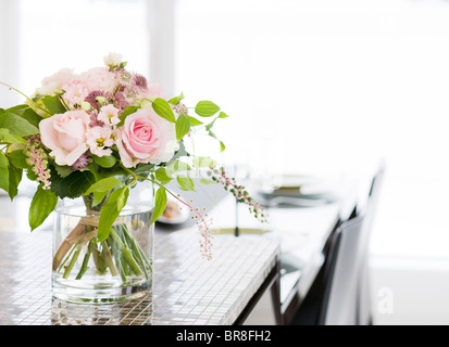 A Bunch of Flowers in a Vase at Dining Table - Stock Photo
