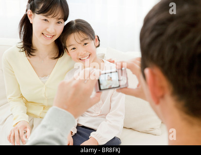 Father taking a photograph of mother and daughter