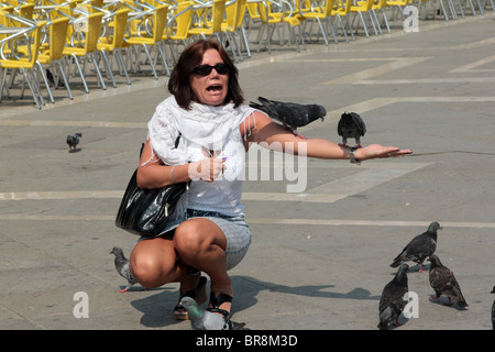 A tourist feeding the pigeons in St Marks square in Venice - Stock Photo