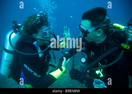 SCUBA divers giving hand signals underwater. - Stock Photo