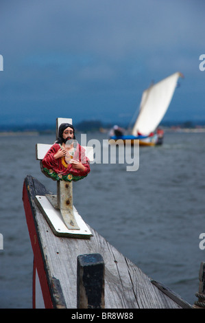 Cross with Jesus Christ  on a traditional Moliceiro boat bow with an out-of-focus Moliceiro boat in the background, - Stock Photo