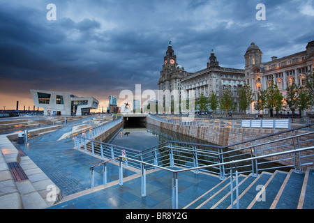 A dramatic stormy evening sky over Liverpool's Three Graces, Ferry Terminal and Canal Link on the Waterfront - Stock Photo
