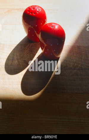 A pair of salt and pepper pots, ceramic, pottery, bright red with white dots, deep graphic shadows on a wooden chopping - Stock Photo