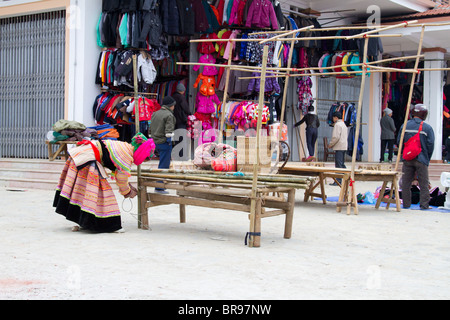 A Flower Hmong woman sets up her stall at the Sunday market in Bac ha, Vietnam - Stock Photo