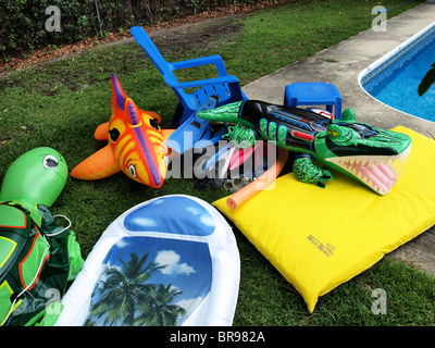 children's pool swimming toys floaters blown-up inflatable sitting beside the edge of a garden backyard with croc - Stock Photo