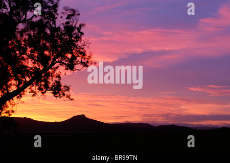 Red sky at dawn with the sun just about to rise over Roseberry Topping in the North York Moors national park Stock Photo