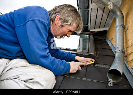 A plumber repairing the leaky roof and drainpipe - Stock Photo