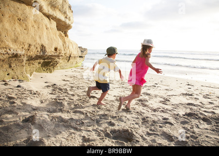 Boy and girl running in the sand on the beach - Stock Photo