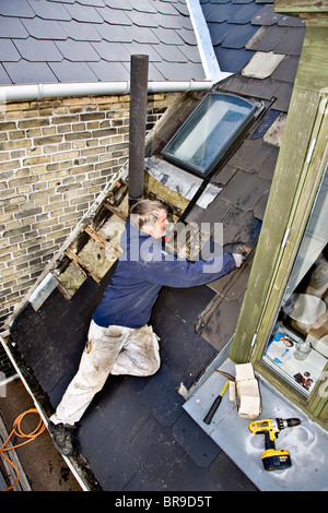 Leaky Roof a plumber replace old leaky roof with new slates stock photo