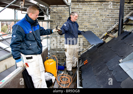 Two plumbers on the scaffold replacing old leaky roof with new slates - Stock Photo
