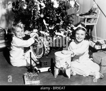1950s SMILING BOY AND GIRL WITH TOYS UNDER TREE CHRISTMAS MORNING - Stock Photo