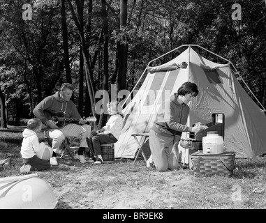 1960s FAMILY CAMPING TENT MOTHER COOKING FATHER PLAYING GUITAR - Stock Photo