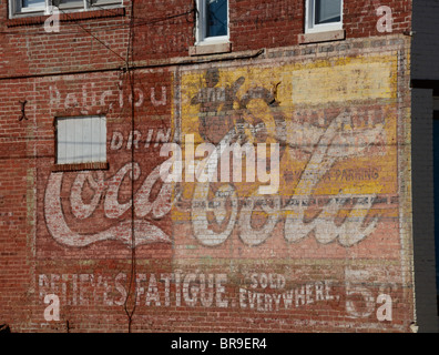Very old ad  for Coca-Cola and Yamaha Motorcycles painted on side of a old brick building. - Stock Photo