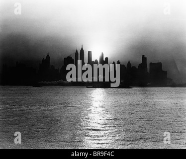 1930s 1940s EARLY MORNING MISTY SUNRISE NEW YORK CITY WITH TUG BOAT BARGE IN HUDSON RIVER - Stock Photo