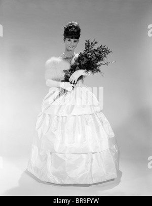 1960s PRETTY YOUNG WOMAN IN EVENING DRESS AT  BEAUTY PAGEANT WEARING FUR STOLE AND TIARA HOLDING BOUQUET OF ROSES - Stock Photo