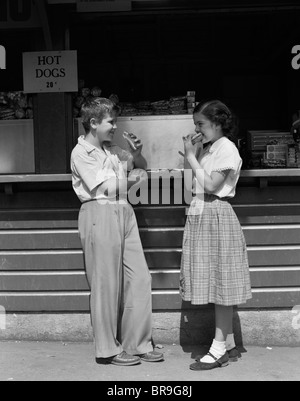 1950s BOY GIRL EATING HOT DOGS AT TAKE OUT STAND - Stock Photo