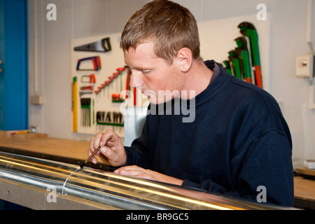 Young plumber making a gutter at the workshop - Stock Photo