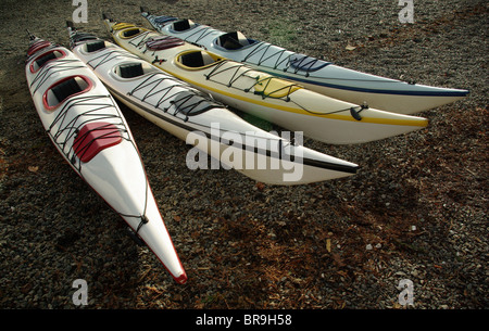 4 two person kayaks resting on rocky shore - Stock Photo
