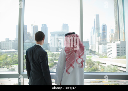 Western and middle eastern businessmen by window of dubai office - Stock Photo