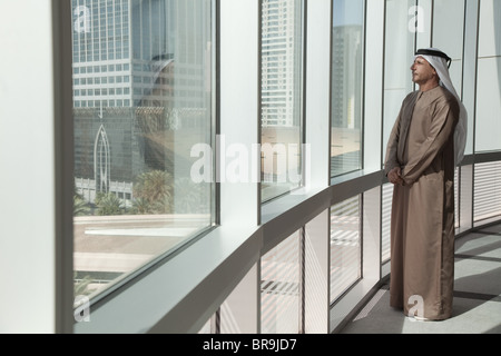 Middle eastern businessman looking out of office window - Stock Photo