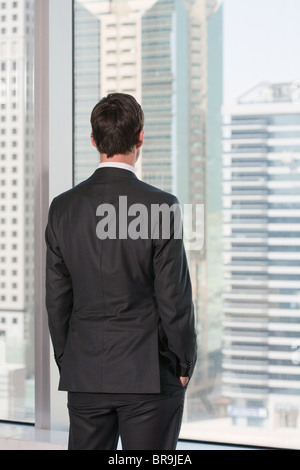 Rear view of businessman looking out of office window - Stock Photo