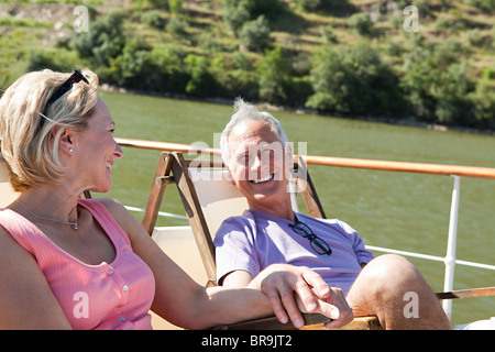 Senior couple sitting on deckchairs on a boat - Stock Photo