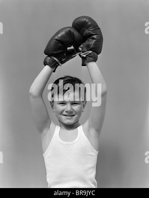 1940s BOY CHILD WINNER WEARING BOXING GLOVES HOLDING HANDS ABOVE HEAD LOOKING AT CAMERA - Stock Photo
