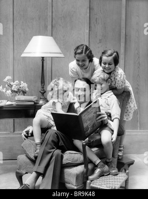 1930s FATHER READING TO FAMILY IN CHAIR - Stock Photo