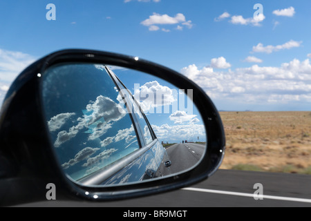 Side view mirror showing cars on the road and clouds reflecting on side of car - suggests moving on from the past - Stock Photo