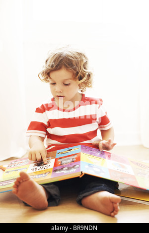 Little boy in red and white striped shirt reading a book - Stock Photo